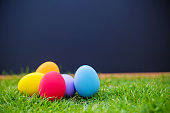Focus colorful easter eggs on grass with blackboard background. symbol of easter's festival. natural background. festive wallpaper. image for background, wallpaper,article,illustration and copy space.