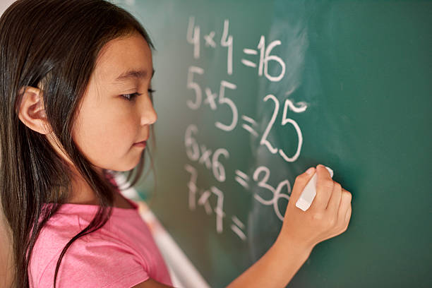 focus girl trying to solve mathematical equation - mathematisches symbol stock-fotos und bilder