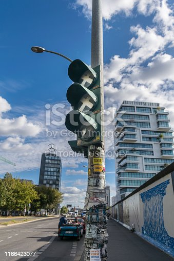 BERLIN, GERMANY - September 26, 2018: Focus in a vandalized traffic light at Breitscheidplatz, near the East Side Gallery with the the Mercedes Benz building and a trabi-safari car in the background.