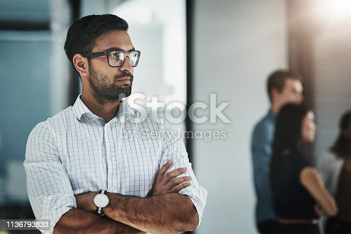 Shot of a young businessman posing with his arms folded in a modern office with his colleagues in the background