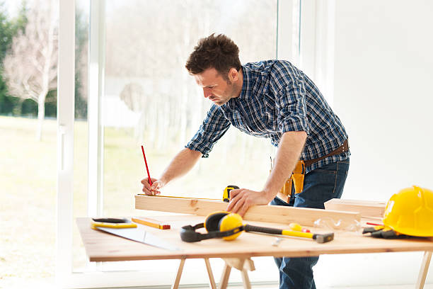 Focus man measuring wooden planks stock photo