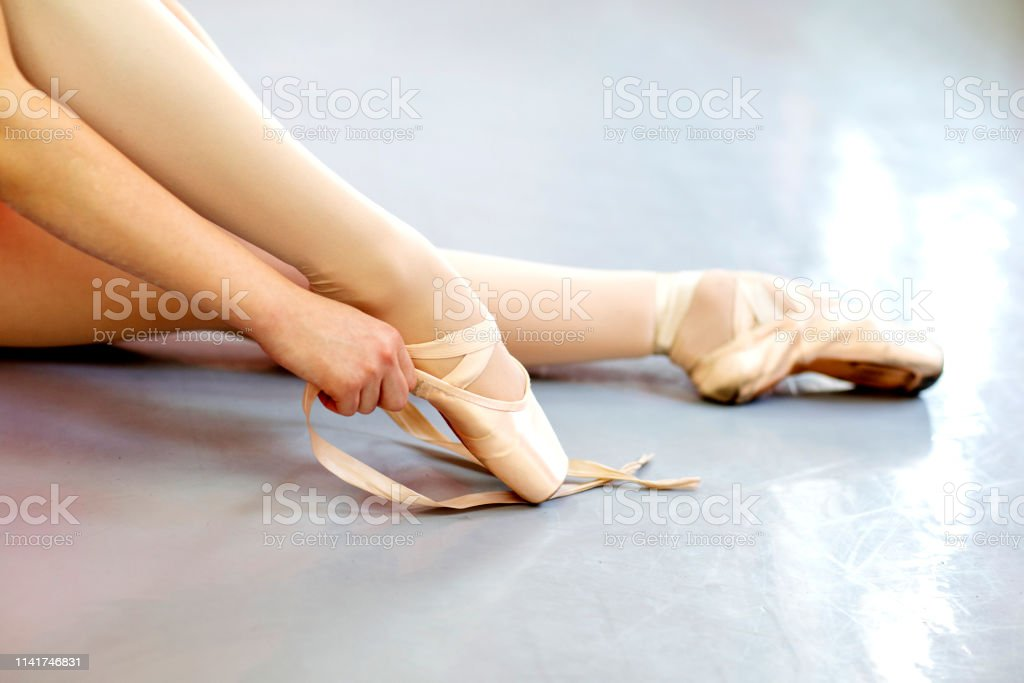 Focus on ballet dancer legs who tie shoelace while sitting on the...