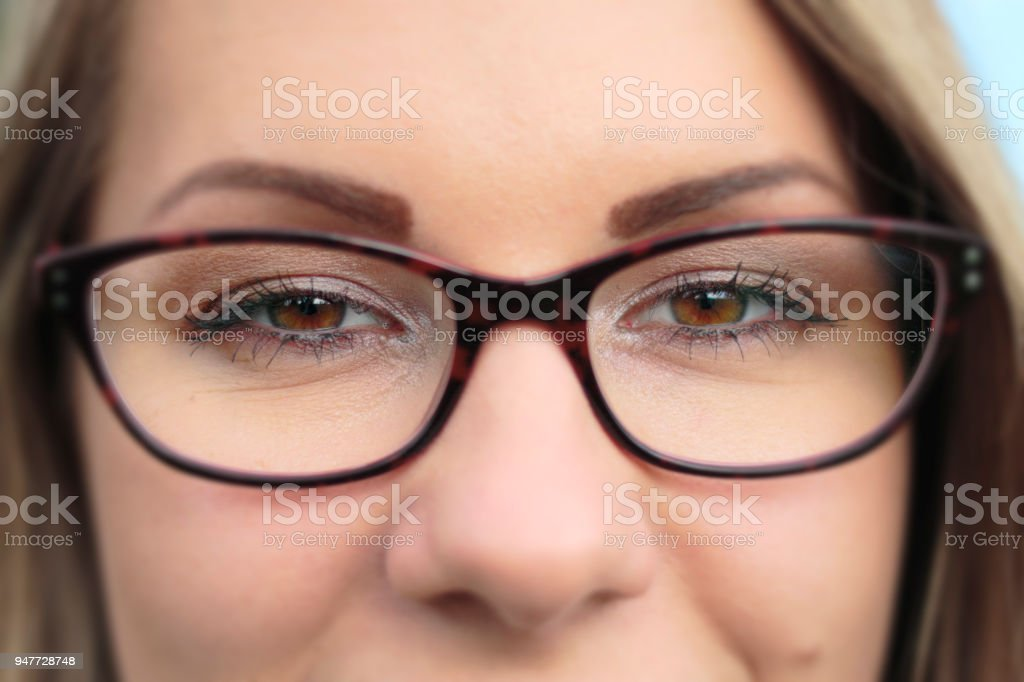 Focus on brown eyes tortoiseshell spectacles close up stock photo