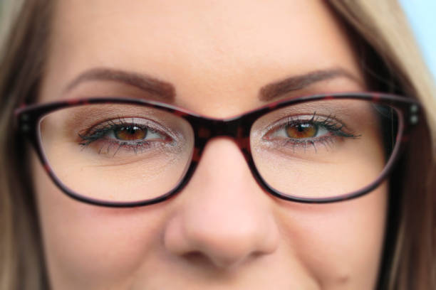 focus on brown eyes tortoiseshell spectacles close up - whiteway polish outdoor girl stock photos and pictures