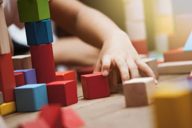 Centrarse en la mano del niño jugando con bloques de madera coloridos - foto de stock