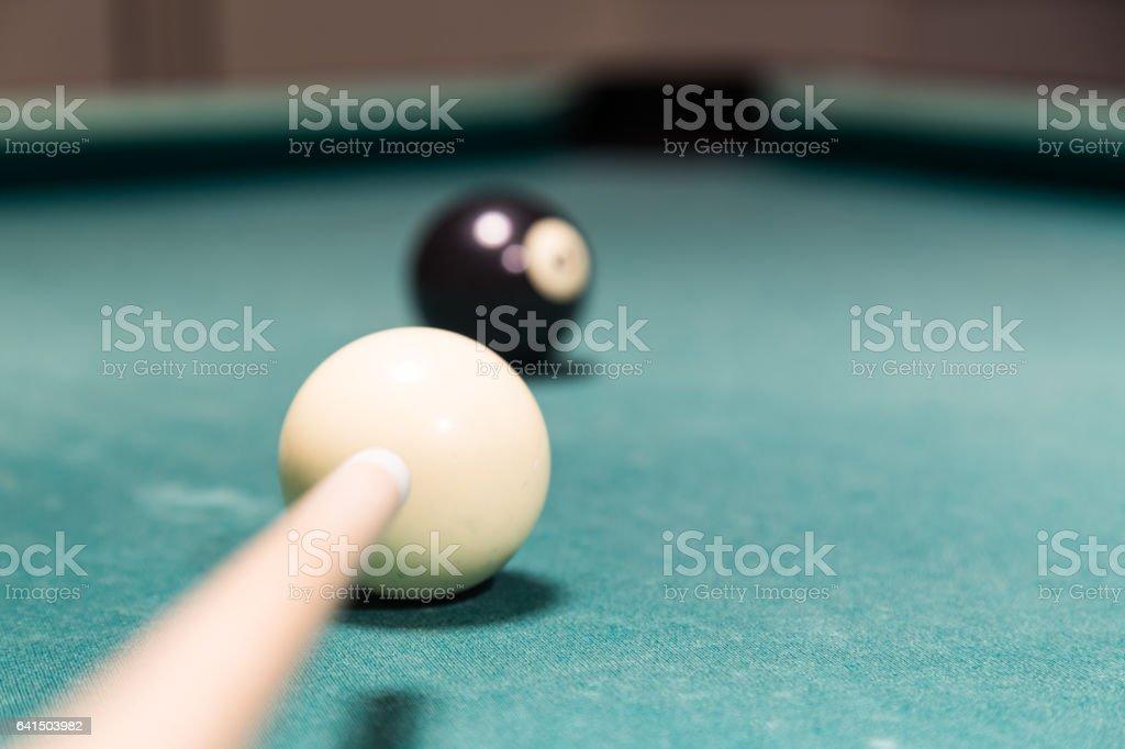 Focus on cue aiming black ball into snooker billards pocket stock photo