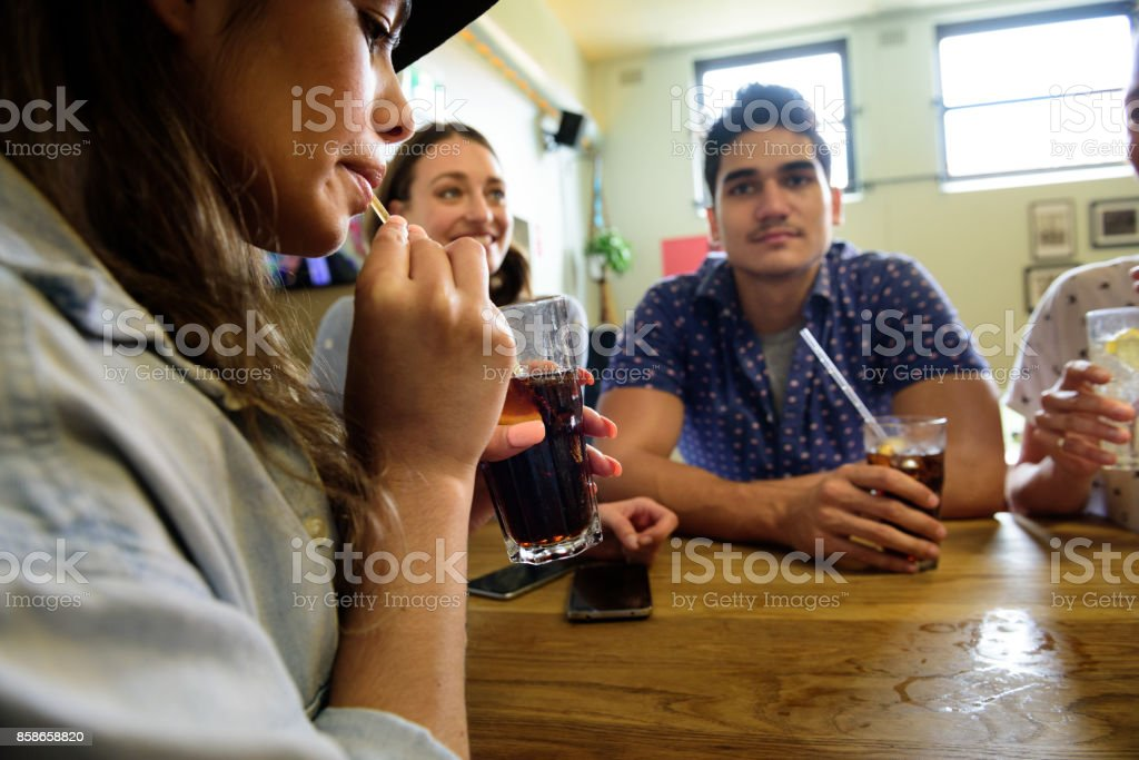 Focus on drink, friends in bar stock photo