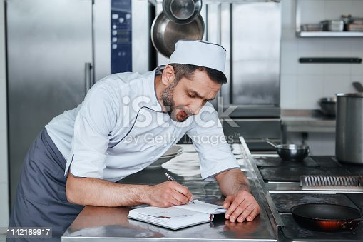 Concentrated male chef cook with grocery list or bills doing inventory at restaurant kitchen. Cooking and people concept. Side view