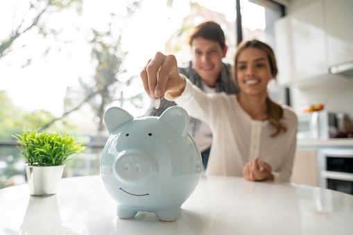 Focus on foreground of latin american young couple saving coins into piggy bank - Lifestyles