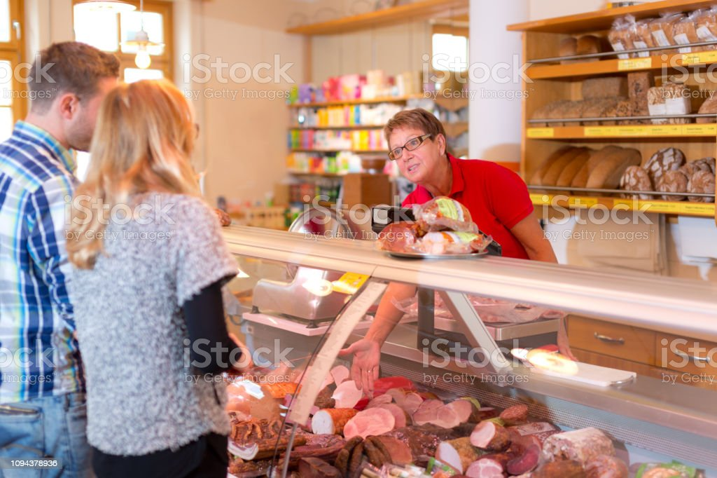 friendly senior older sales clerk woman offering sausage at the cold...