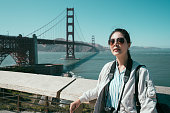 focus on girl face camera wearing sunglasses with attractive smile relying on wooden handrail with golden gate bridge in background. young female backpacker sightseeing travel tour america in summer.