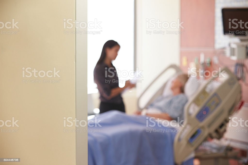 Focus On Hospital Room Sign With Doctor Talking To Patient stock photo