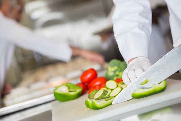 Focus on knife chopping vegetables in commercial kitchen stock photo