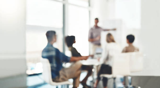 Focus on making a success of the day Defocused shot of a group of businesspeople having a meeting in an office collaboration stock pictures, royalty-free photos & images