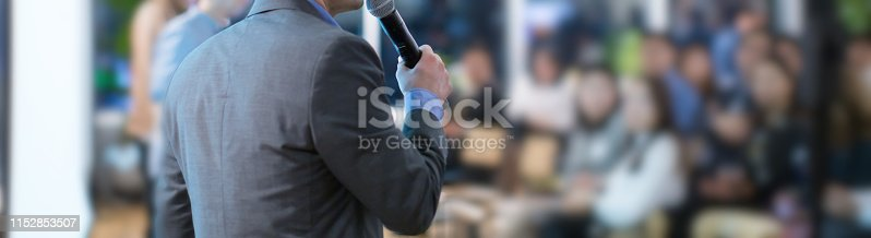 istock Focus on microphone held by panel speaker on stage during presentation. Executive manager presenter at corporate conference talking to audience.  Business leadership CEO lecture during seminar. 1152853507