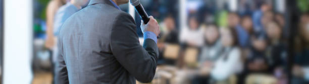 Focus on microphone held by panel speaker on stage during presentation. Executive manager presenter at corporate conference talking to audience.  Business leadership CEO lecture during seminar. Speaker and very blurred audience debate stock pictures, royalty-free photos & images