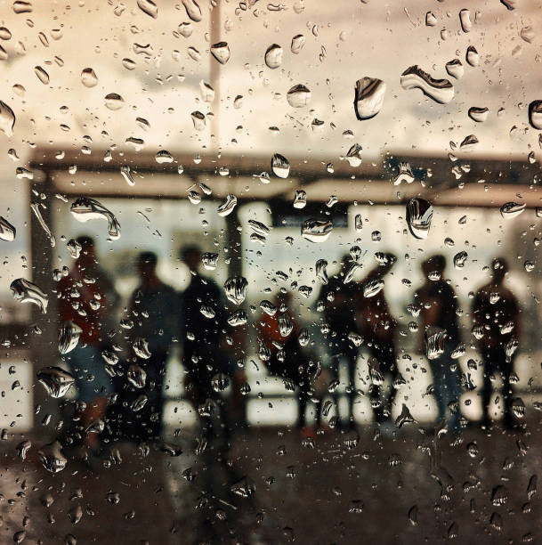 Focus on raindrops and the people waiting for bus