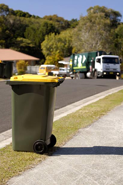 Focus on Rubbish bin with rubbish truck approaching bins stock photo