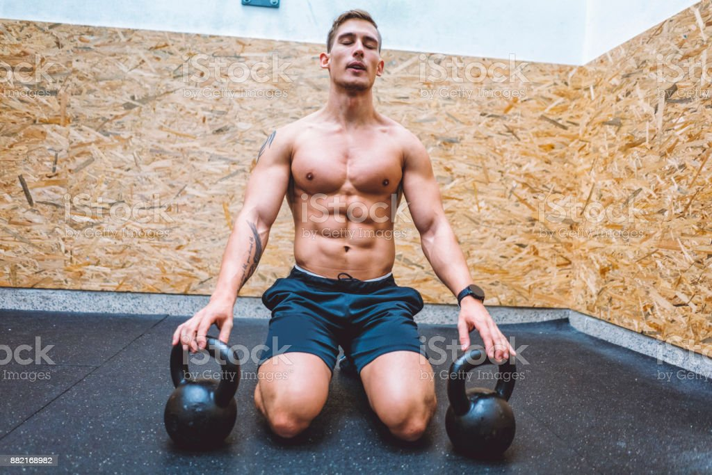 Strong young and muscular man being shirtless in the gym, wearing...
