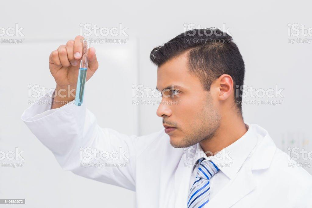 Focus scientist looking at blue precipitate stock photo