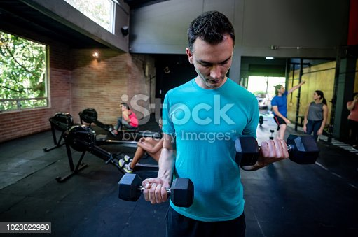 Focused adult man doing arms workout with freeweights and other people exercising at the background