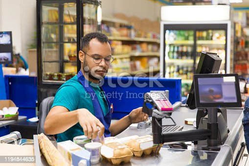 Focused African American cashier scanning goods at checkout. Concentrated young man in eyeglasses at workplace. Shopping concept