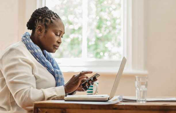 Fokussierte afroamerikanische Unternehmerin mit ihrem Handy zu Hause – Foto
