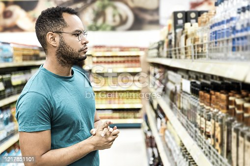 Focused African American man choosing alcohol drinks. Serious bearded guy standing in aisle and looking at drinks. Shopping concept