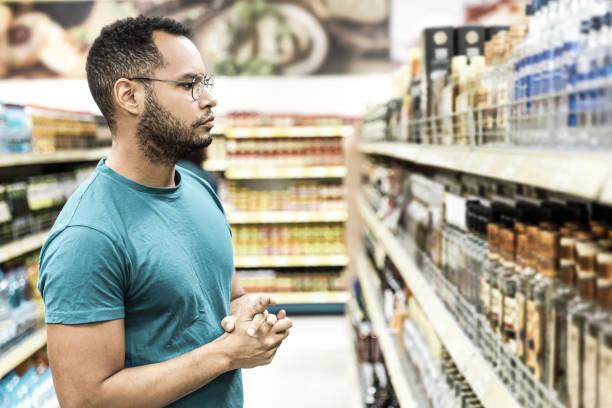 Focused African American man choosing alcohol drinks stock photo