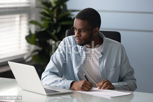 istock Focused african American man make notes watching webinar on laptop 1189709716