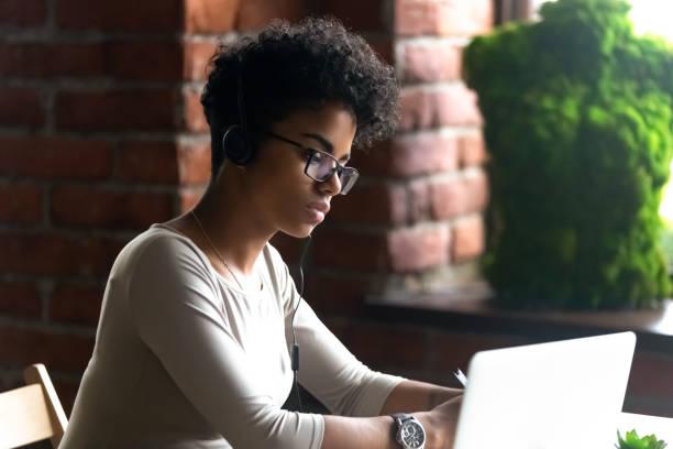konzentrierte sich afrikanische amerikanische frau, die mit kopfhörern mit laptop - nachrichten video stock-fotos und bilder