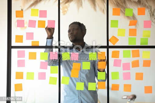 istock Focused african businessman checking project progress on sticky notes 1182967364