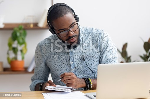 istock Focused african businessman in headphones writing notes watching webinar 1150384596
