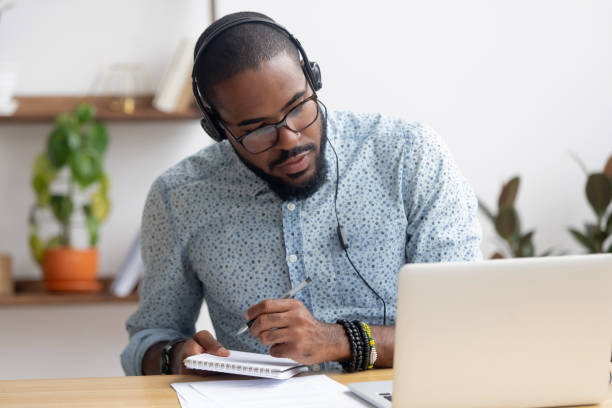 focused african businessman in headphones writing notes watching webinar - подготовка стоковые фото и изображения