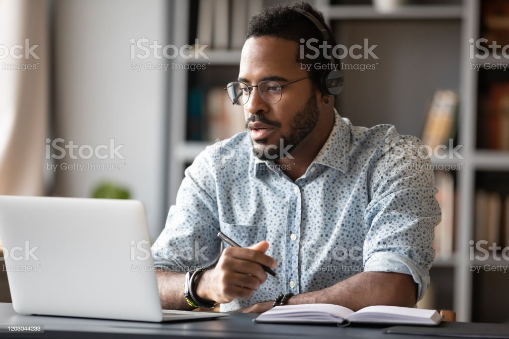 Focused african businessman wear headphones study online watching webinar Focused young african businessman wear headphones study online watching webinar podcast on laptop listening learning education course conference calling make notes sit at work desk, elearning concept Adult Stock Photo
