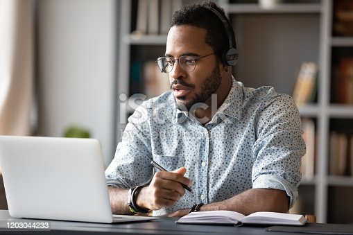 Focused young african businessman wear headphones study online watching webinar podcast on laptop listening learning education course conference calling make notes sit at work desk, elearning concept