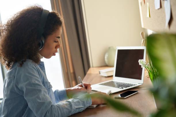 集中したアフリカの女子学生は、ホームオフィスのデスクで一人で勉強するヘッドフォンを着用しています。ミレニアル世代の混血ティーンガールリスニングオーディオポッドキャストeノー - gen z ストックフォトと画像