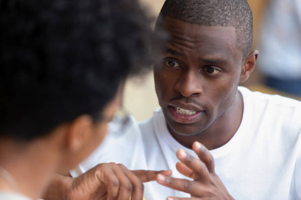 Focused african man having serious talk with woman at meeting Focused african american man looking speaking to woman having business talk negotiating explaining, serious black guy having conversation with girlfriend friend discussing important issues at meeting persuasion stock pictures, royalty-free photos & images