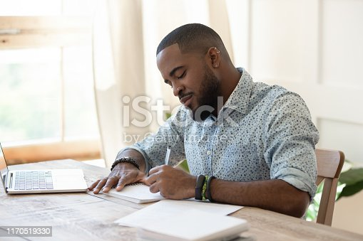 1174436608 istock photo Focused african man student freelancer making notes studying with laptop 1170519330