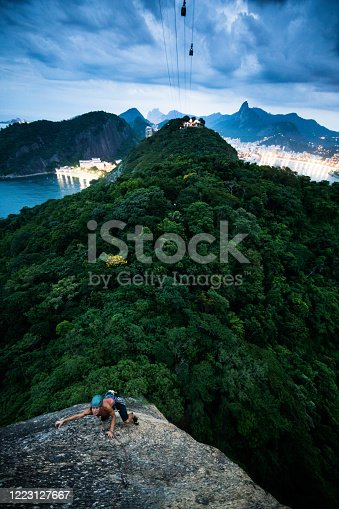 Focused and motivated young female rock climber in Rio De Janeiro Brazil on Sugarloaf mountain