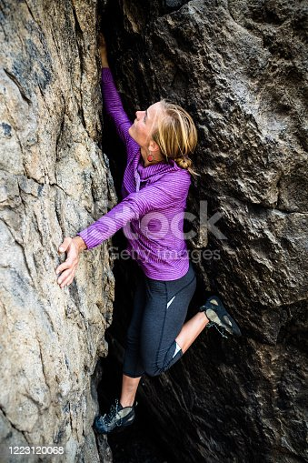 Focused and motivated young female rock climber female rock climber bouldering in Montana