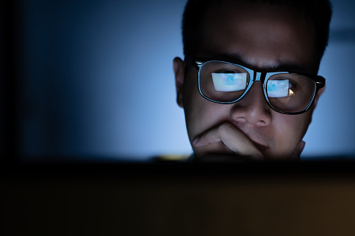 A focused and serious looking man working and thinking hard on a computer