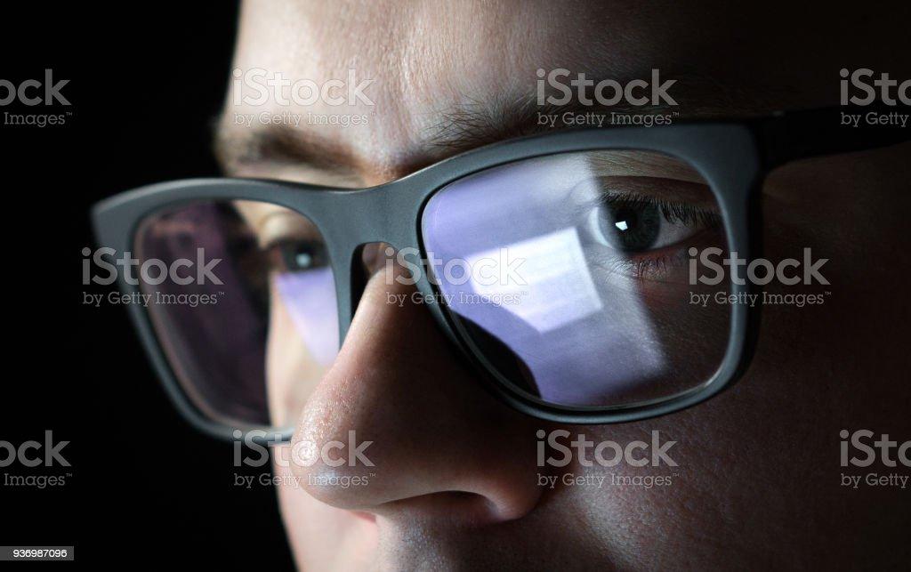 Hombre centrado y reflexivo. Programador, programador o desarrollador usando laptop en oscuridad. Hombre de negocios trabajando tarde. Estudiante por la noche. - foto de stock
