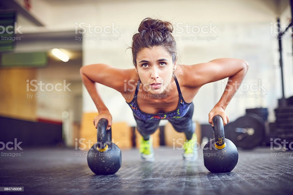 Focused athlete doing push-ups on kettlebells in gym stock photo