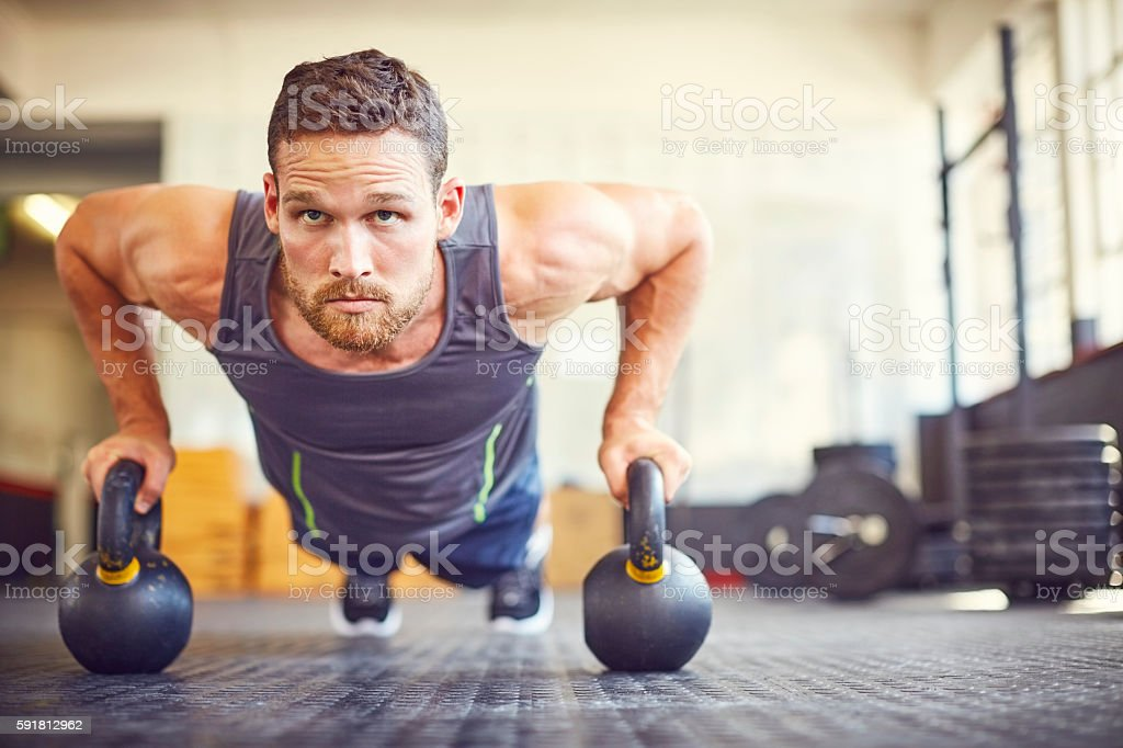 Focused athlete doing push-ups on kettlebells in gym – Foto