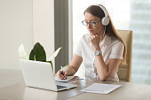istock Focused attentive woman wearing headphones using laptop at office desk 828110476