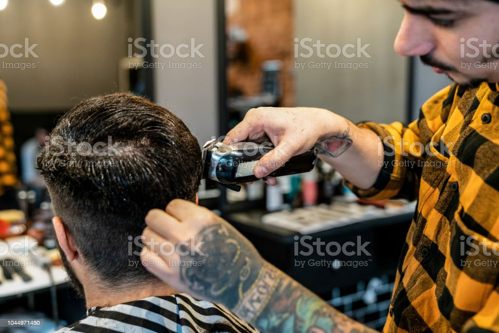 Focused barber using an electric razor to cut male customers hair at...