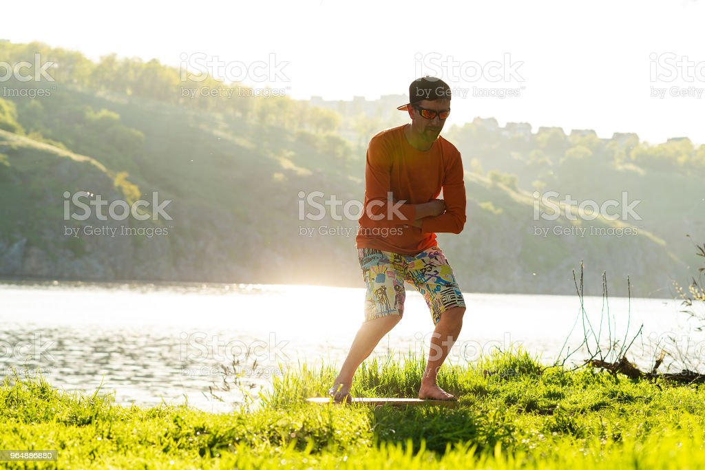 Focused bearded man is training on the balance board royalty-free stock photo