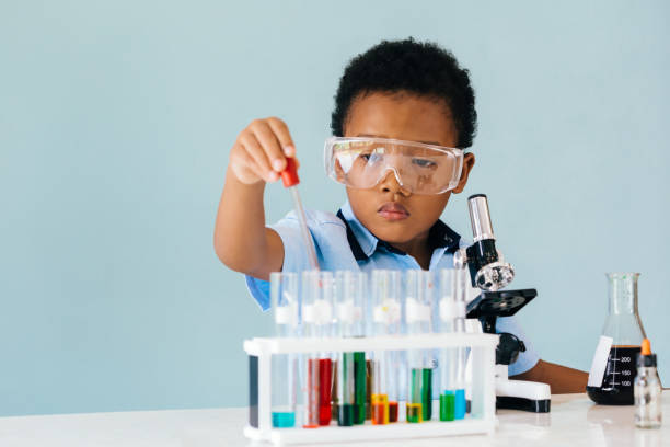 Focused black boy learning to mix chemicals stock photo
