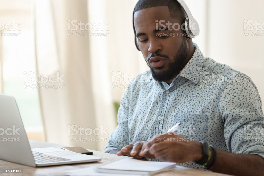 Focused black guy busy with certification training. - Royalty-free Adult Stock Photo
